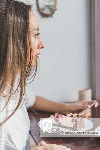 Frau isst Kuchen in einem Café