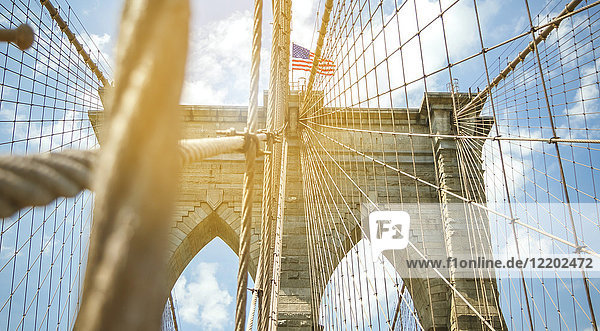 USA  New York  Brooklyn  Close up of Brooklyn Bridge metal cables and arches with american flag on the top
