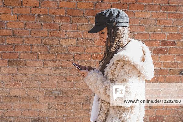 Stilvolle junge Frau vor der Ziegelwand mit dem Handy