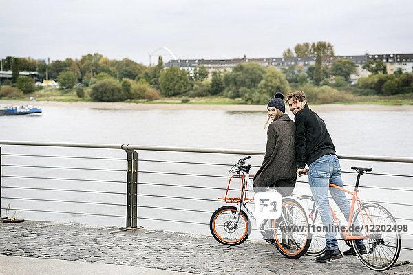 Lächelndes Paar mit Fahrrädern am Flussufer