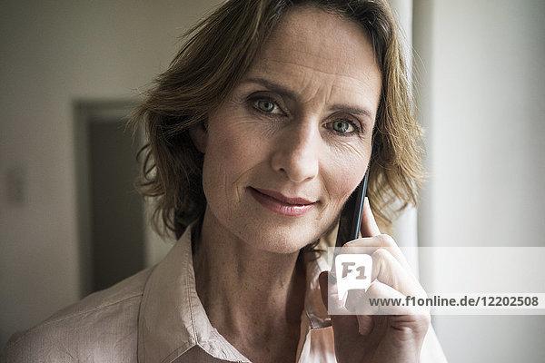 Porträt der lächelnden reifen Frau auf dem Handy