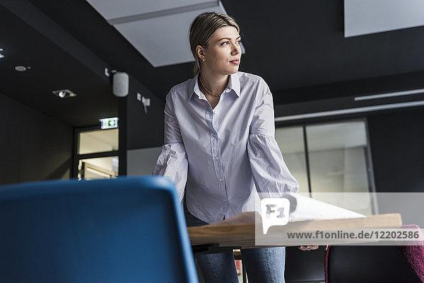 Junge Frau am Tisch stehend im Büro denkend