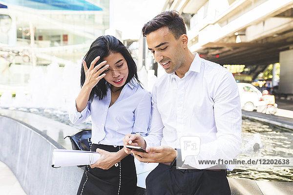 Thailand  Bangkok  Geschäftsmann und Geschäftsfrau in der Stadt mit Handy