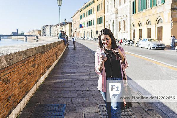 Junge Geschäftsfrau mit ihrem Smartphone in der Stadt