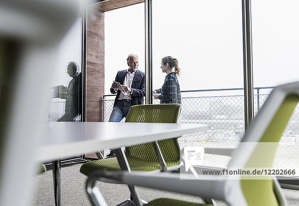 Geschäftsmann und junge Frau im Gespräch auf dem Bürobalkon
