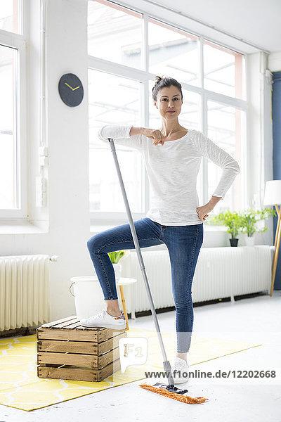 Porträt einer selbstbewussten Frau  die zu Hause den Boden wischt.
