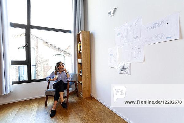 Junge Architektin im Büro mit Blick auf die Pinnwand