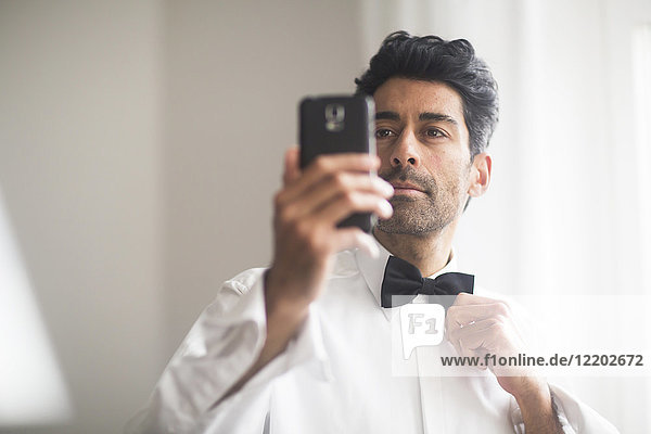 Portrait of man using cell phone for adjusting his bow tie