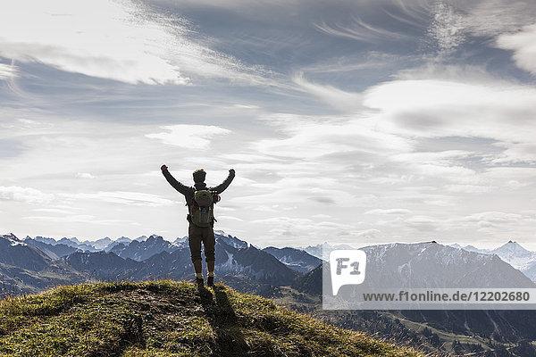 Österreich  Tirol  junger Mann  der in der Berglandschaft steht und jubelt