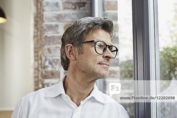 Erwachsener Geschäftsmann mit Brille  der aus dem Fenster schaut.