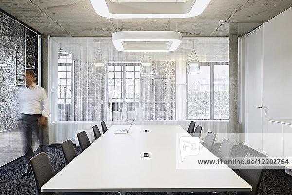 Geschäftsmann zu Fuß im modernen Konferenzraum