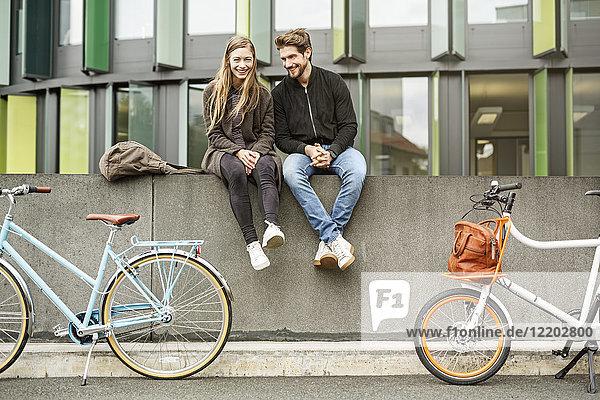 Glückliches Paar mit Fahrrädern an der Wand sitzend