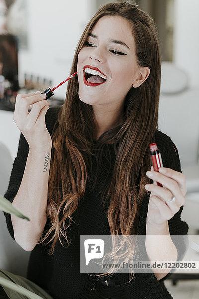 Porträt einer glücklichen jungen Frau mit Lippenstift