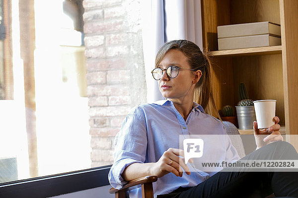 Young woman with coffee cup looking out of office window