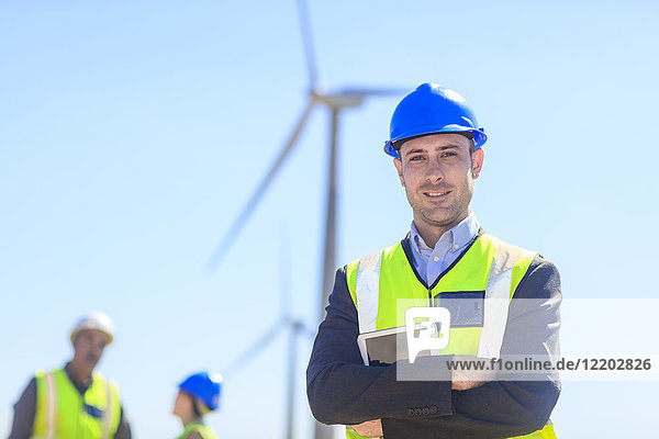 Portrait of confident businessman wearing reflective vest on a wind farm