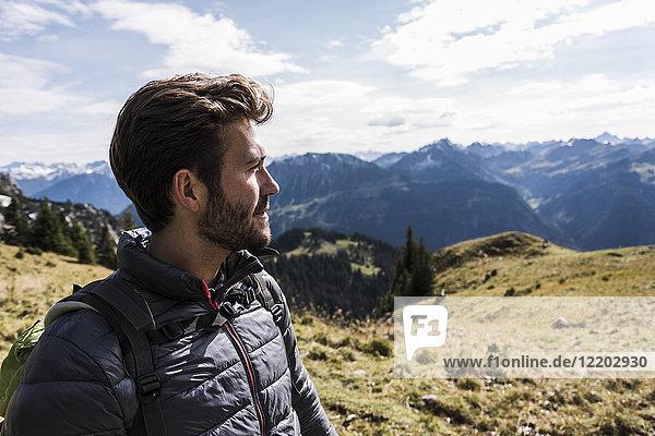 Österreich  Tirol  Porträt eines jungen Mannes in der Bergwelt mit Blick auf die Landschaft