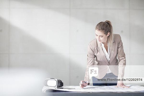 Junge Frau mit Blaupause und VR-Brille auf Tisch im Büro