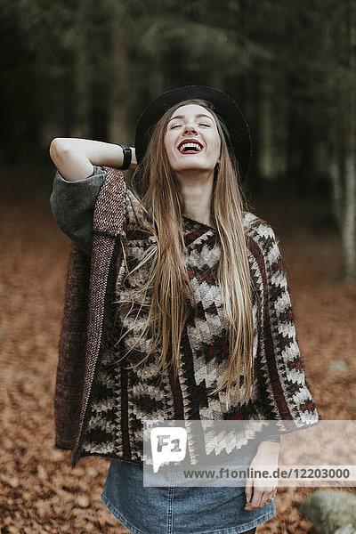 Porträt der lachenden jungen Frau mit Hut und Poncho im Herbstwald