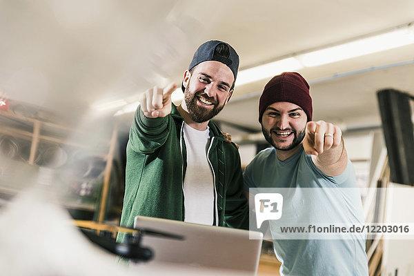 Porträt von zwei glücklichen jungen Männern in der Werkstatt