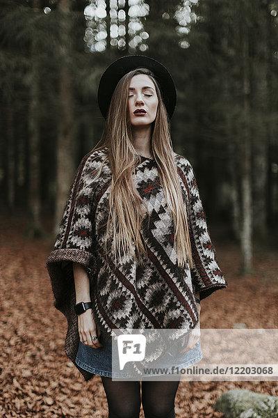 Porträt einer jungen Frau mit Hut und Poncho im herbstlichen Wald