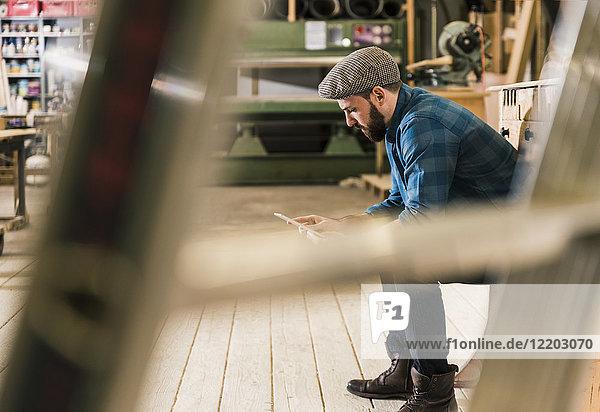 Mann sitzt in der Werkstatt mit Tablette