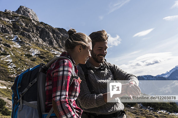 Österreich  Tirol  lächelndes junges Paar beim Betrachten der Uhr in der Bergwelt