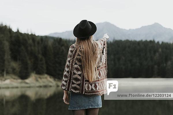 Rückansicht der modischen jungen Frau mit Hut und Poncho vor dem See