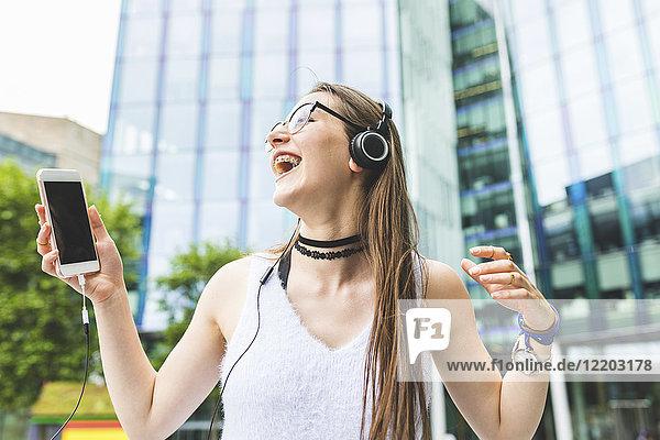 Fröhliches Teenagermädchen mit Handy und Kopfhörer in der Stadt