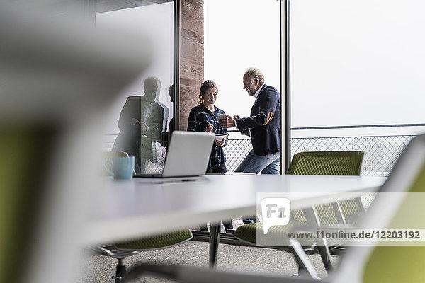 Erwachsener Geschäftsmann mit Handy und junger Frau auf dem Bürobalkon