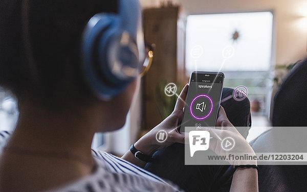 Frau sitzt zu Hause mit Kopfhörer und benutzt das Smartphone als Fernbedienung.
