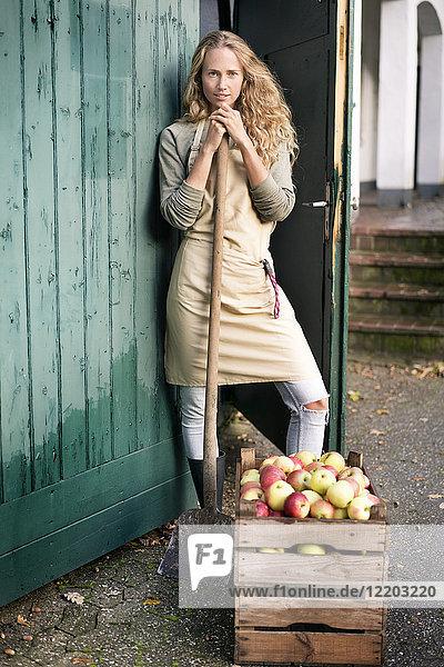 Porträt einer selbstbewussten Frau  die an einer Kiste mit Äpfeln steht.