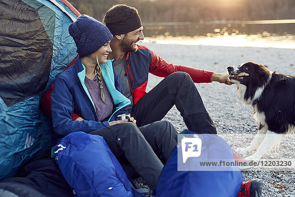 Glückliches junges Paar mit Hund im Zelt am Seeufer
