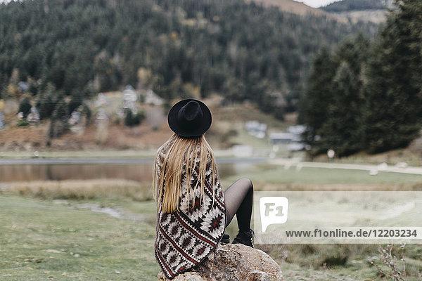 Rückansicht der modischen jungen Frau mit Hut und Poncho auf einem Felsen sitzend