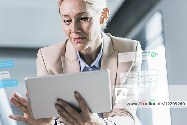 Geschäftsfrau im Büro sitzend  mit digitalem Tablett