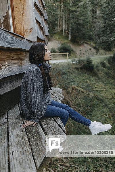 Junge Frau sitzend in einem Holzhaus in der Natur