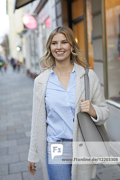 Portrait of smiling woman walking in the city