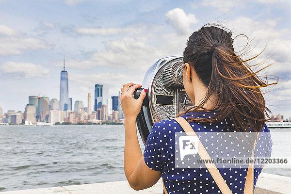USA  New York  Frau mit Blick auf die Skyline von Manhattan mit Münzfernrohr