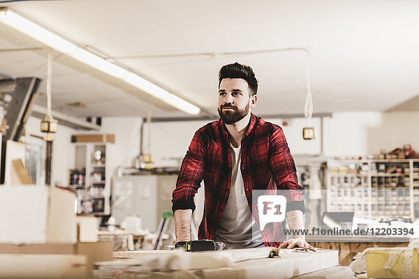 Porträt eines selbstbewussten Mannes in der Werkstatt