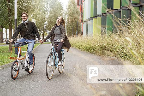 Glückliches Paar  das Hand in Hand auf einer Bahn fährt