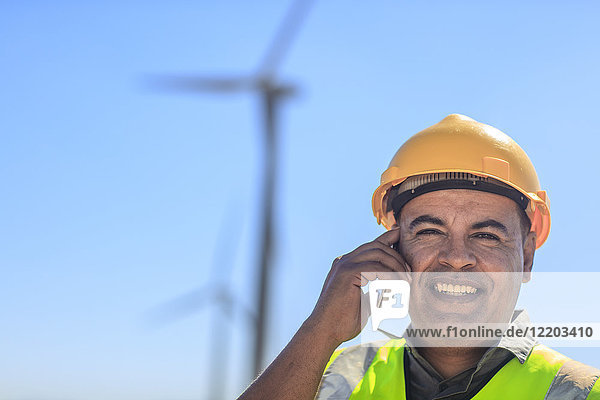 Portrait of smiling technician on cell phone on a wind farm