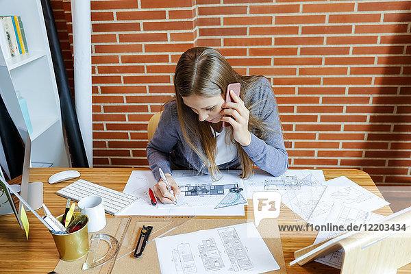 Junge Frau  die im Architekturbüro arbeitet und am Telefon spricht.