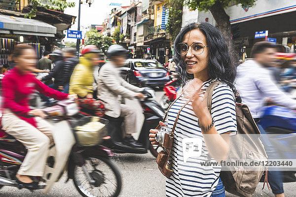 Vietnam  Hanoi  Porträt einer lächelnden jungen Frau im Stadtverkehr