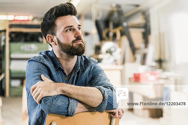 Mann sitzt auf Stuhl in der Werkstatt