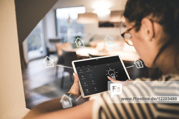 Frau sitzt zu Hause und benutzt ein digitales Tablett  um sein intelligentes Zuhause fernzusteuern.