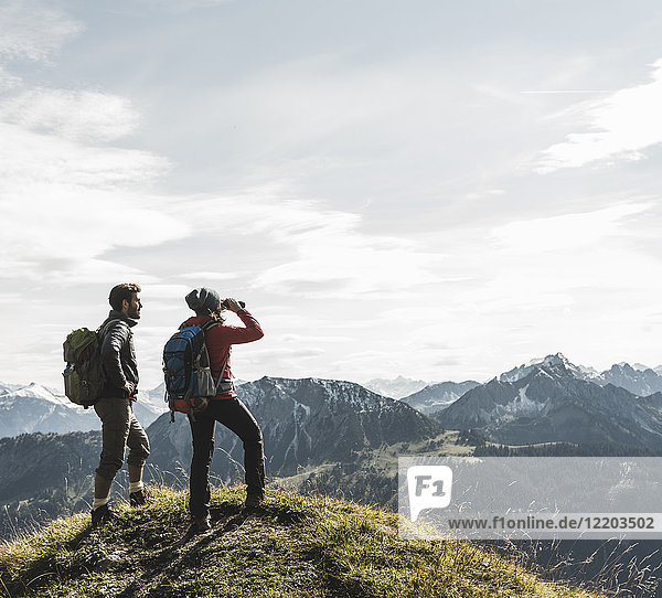 Austria  Tyrol  young couple standing in mountainscape looking at view