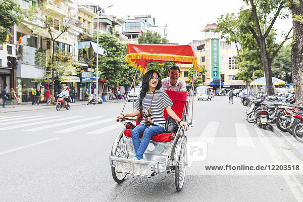 Vietnam  Hanoi  young woman on a riksha exploring the city