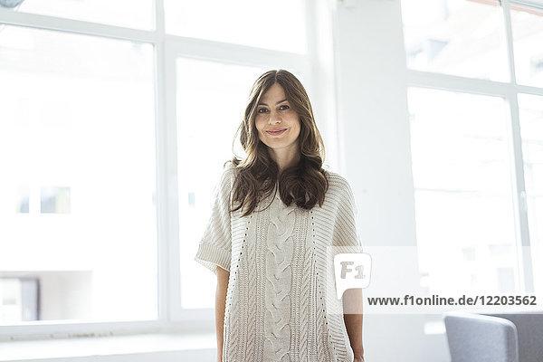Porträt einer lächelnden Frau im hellen Zimmer mit Fenster