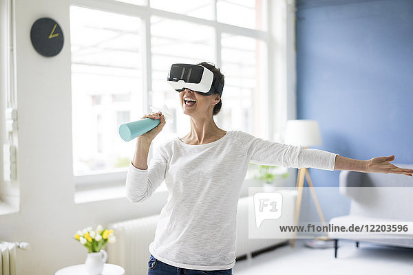 Vital woman at home cleaning wearing VR glasses