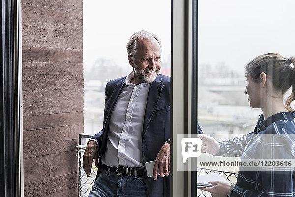 Lächelnder reifer Geschäftsmann und junge Frau im Gespräch auf dem Bürobalkon