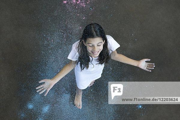 Fröhliches Mädchen beim Duschen von Farbpulver